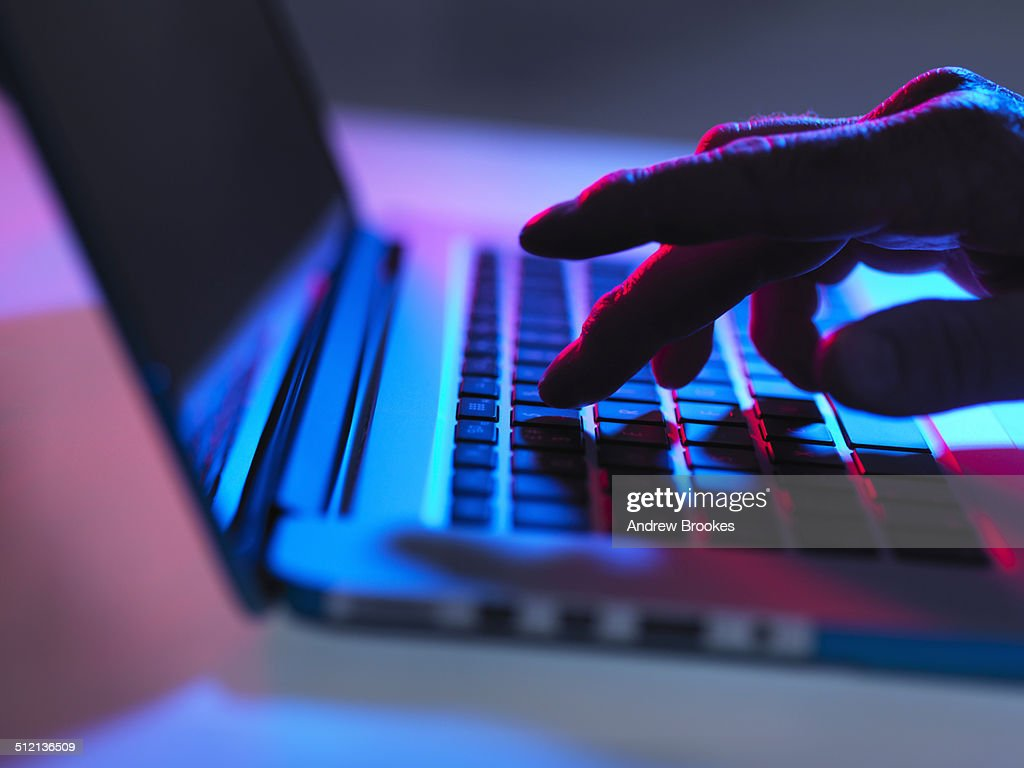 Silhouette of male hand typing on laptop keyboard at night : Stock Photo