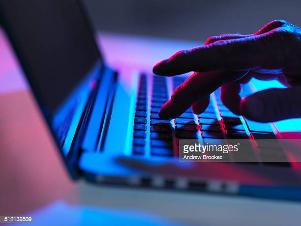 silhouette of male hand typing on laptop keyboard at night - computertoetsenbord stockfoto's en -beelden