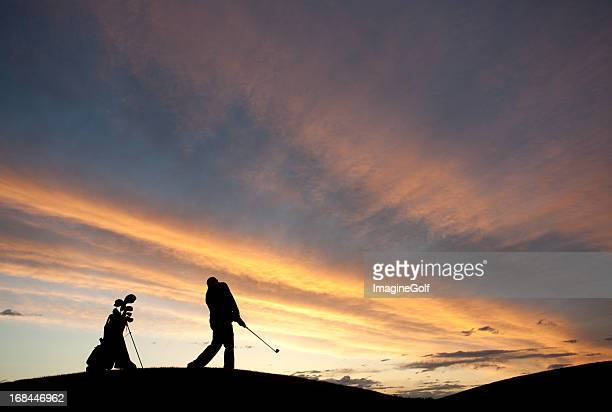 silhouette of male senior golfer swinging golf club - golf background stock photos and pictures