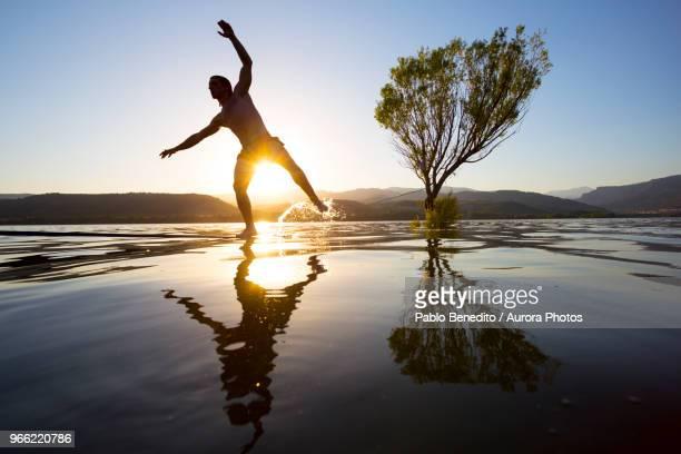 silhouette of male slackliner crossing slackline tensioned over shiny lake at sunset, pobla de segur, lleida, spain - provinz lerida stock-fotos und bilder