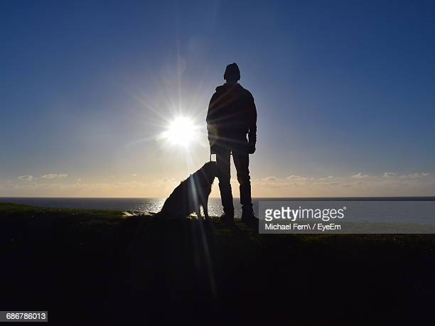 Silhouette Of Man And Dog Standing On Sea Shore At Sunset