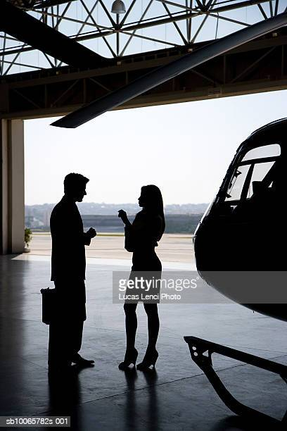 silhouette of man and woman in front of helicopter in hangar - inside helicopter stock pictures, royalty-free photos & images