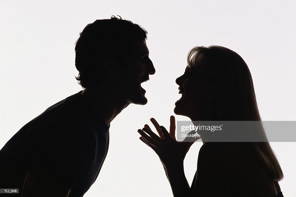 Silhouette of man and woman yelling at each other : Stock Photo