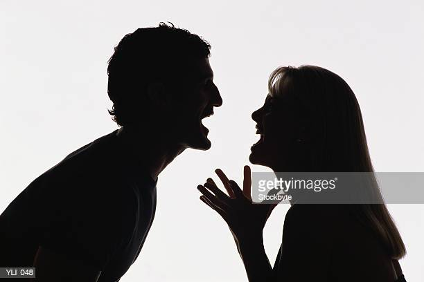 Silhouette of man and woman yelling at each other