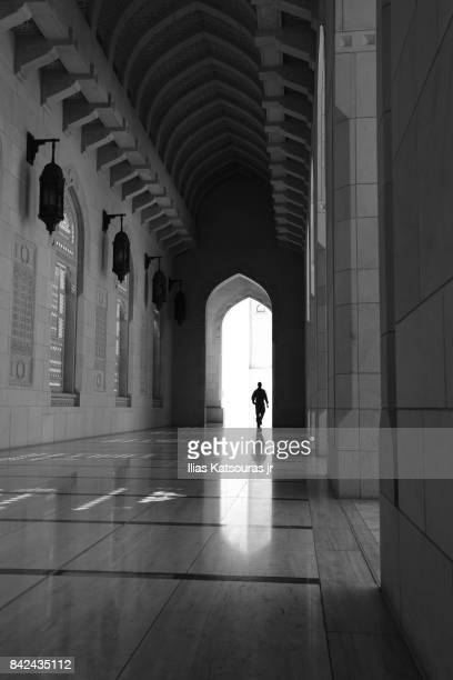 Silhouette of man at arcade at the inner courtyard of the Sultan Qaboos Grand Mosque in Muscat, Oman