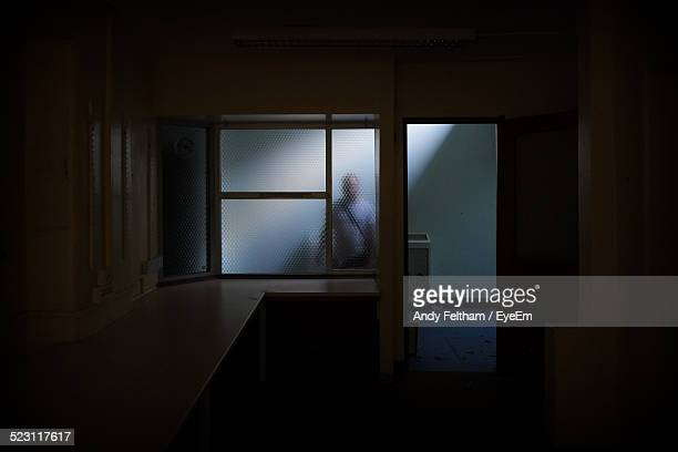 Silhouette Of Man Behind Glass Door In Empty Abandoned Building