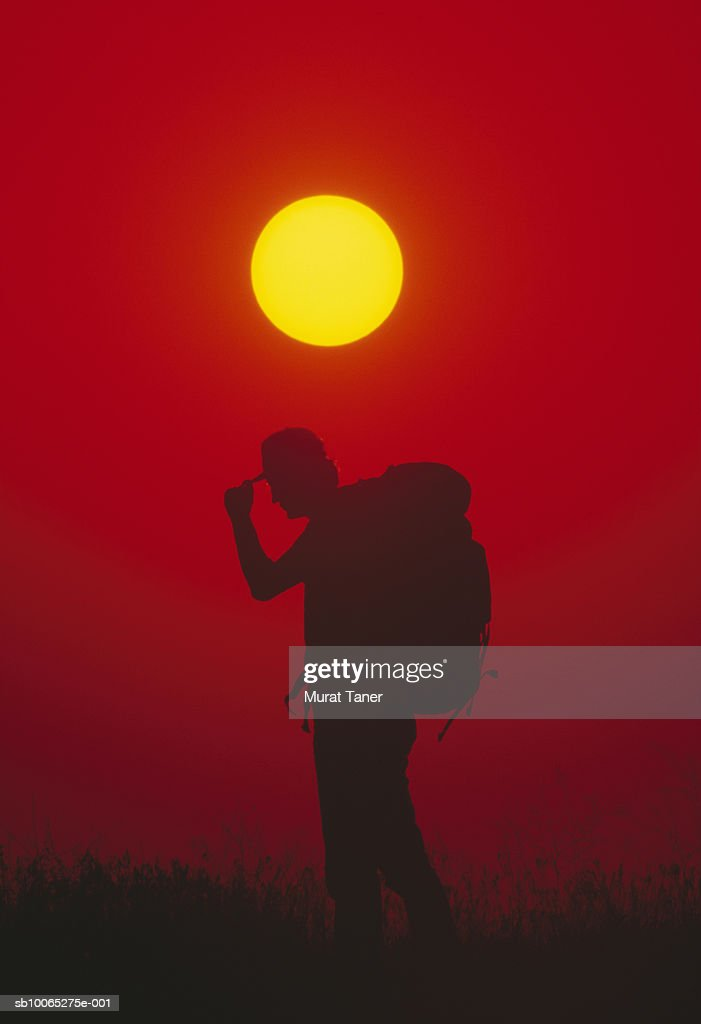 Silhouette of man carrying rucksack and holding cap, sunset : Foto stock