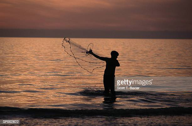 Silhouette of Man Casting Net