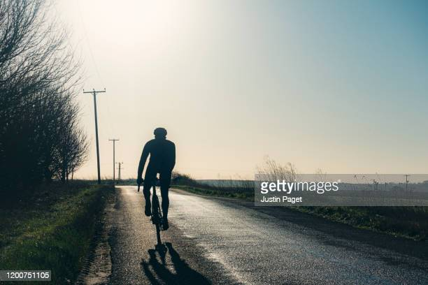 silhouette of man cycling on road - riding stock pictures, royalty-free photos & images