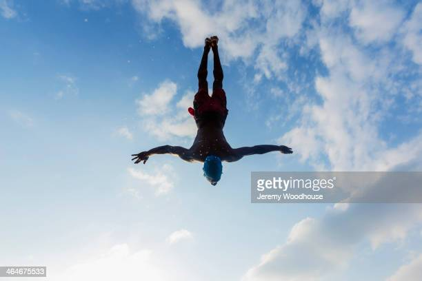silhouette of man diving against blue sky - jeremy woodhouse stock pictures, royalty-free photos & images