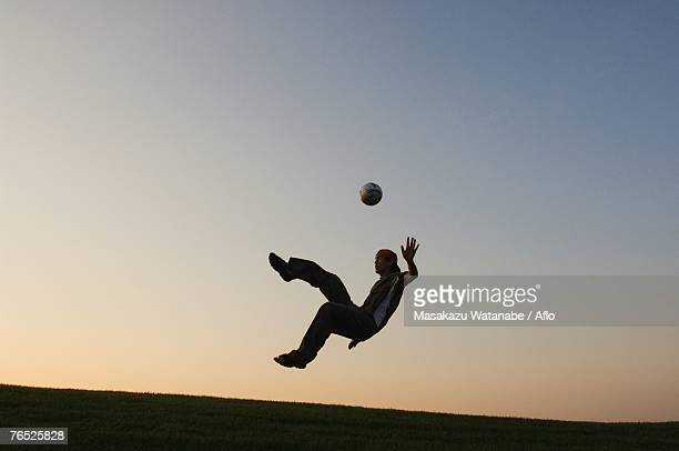Silhouette of man doing a bicycle kick
