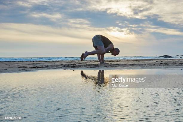 silhouette of man doing 'crow pose yoga' moves on beach - entertainment occupation stock pictures, royalty-free photos & images
