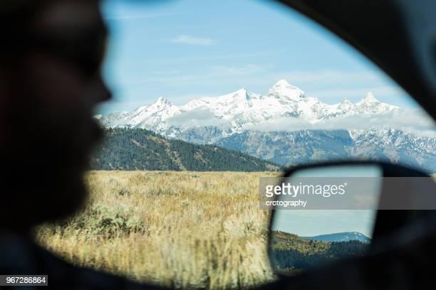 silhouette of man driving past mountain range, wyoming, america, usa - wildnis stock-fotos und bilder