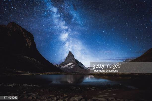 silhouette of man enjoying the milky way and millions of stars above matterhorn and a lake in swiss alps - matterhorn stock pictures, royalty-free photos & images