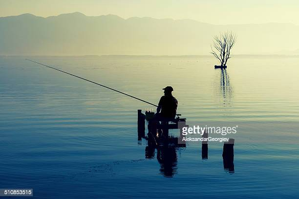 Silhouette of Man Fishing on The Lake at Sunrise