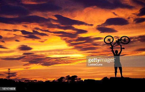 Silhouette of man holding bike above head at sunset