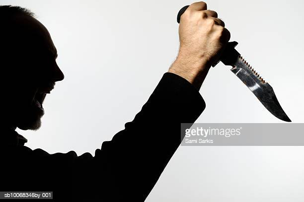 Silhouette of man holding dagger and yelling