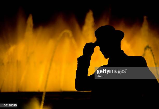 Silhouette of Man Holding Hat Against Colorful Fountain