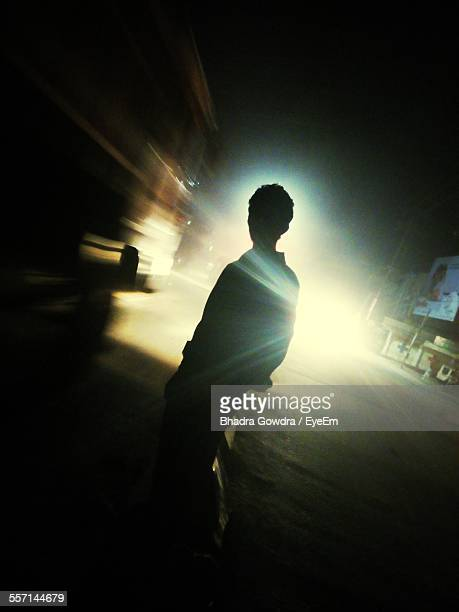 Silhouette Of Man In Cars Headlights On Road