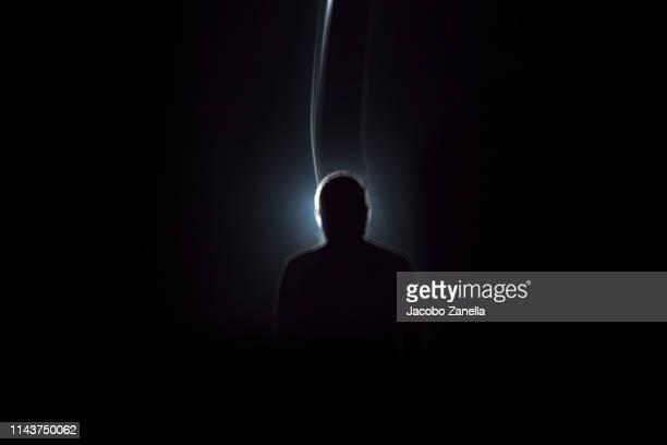 silhouette of man in dark tunnel - 先頭 ストックフォトと画像