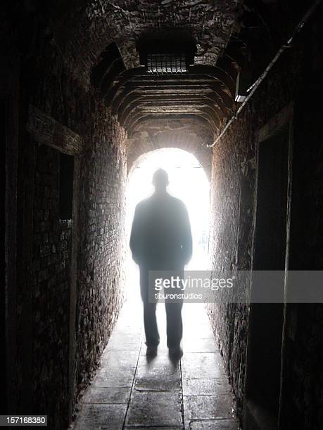 Silhouette of Man in Dark Tunnel with Light at End