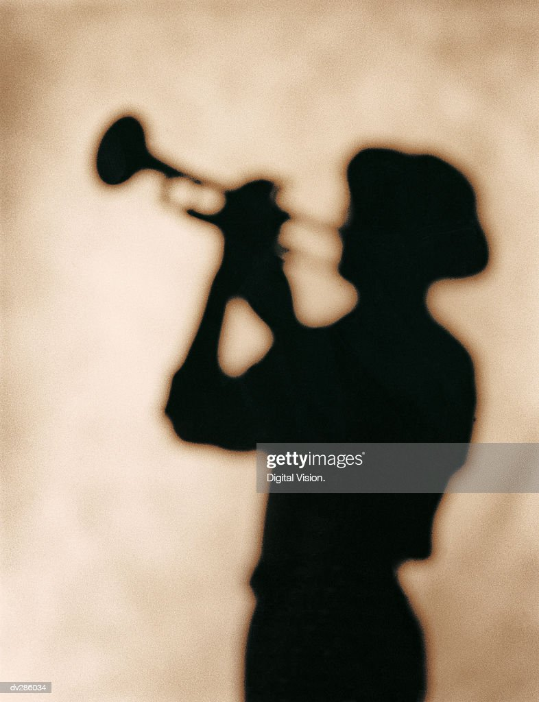 Silhouette of man in hat, playing trumpet : Stock Photo