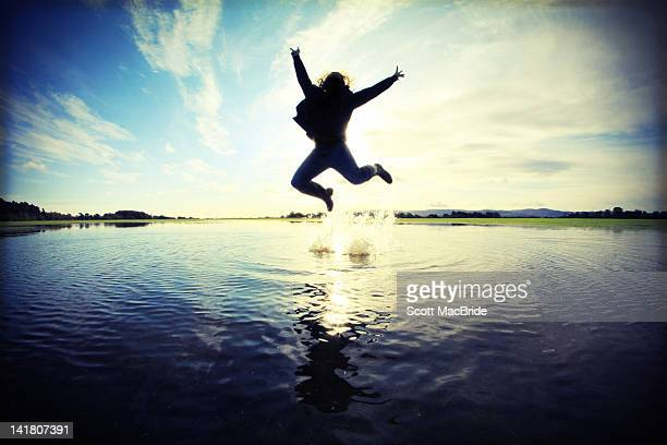 Silhouette of man jumping in puddle