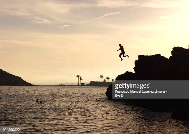 Silhouette Of Man Jumping Over Sea Against Sky During Sunset