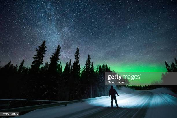 silhouette of man looking atnorthern lights, finland - image stockfoto's en -beelden