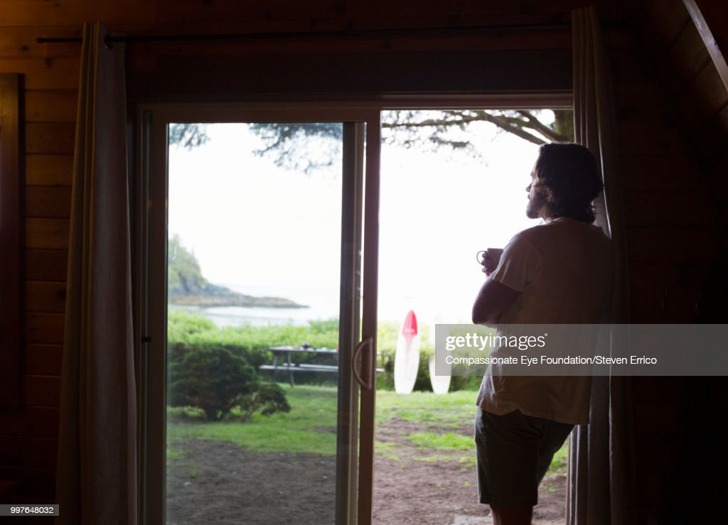 Silhouette of man looking out of window : Stock Photo
