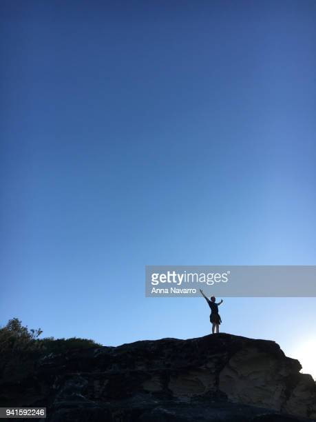 Silhouette of man looking triumphant standing on rock ledge against blue sky