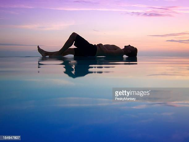 Silhouette of Man Lying Across Sunset Infinity Pool