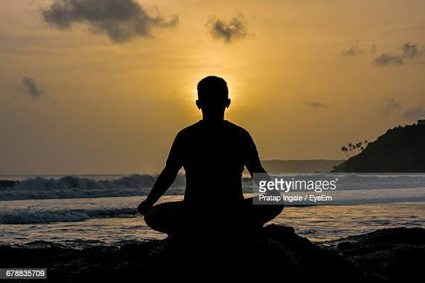 Silhouette Of Man Meditating On Beach