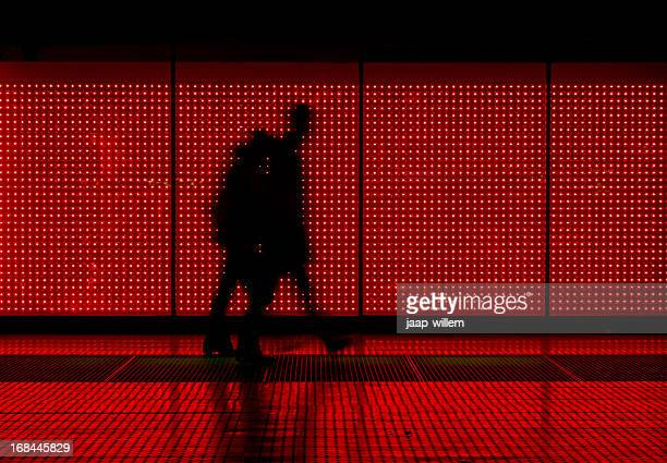 silhouette of man moving in red background - illuminated stock pictures, royalty-free photos & images