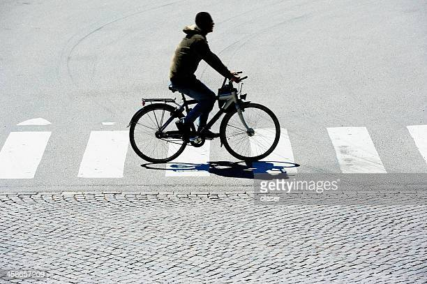 silhouette of man on bicycle in motion - pedestrian crossing stock photos and pictures