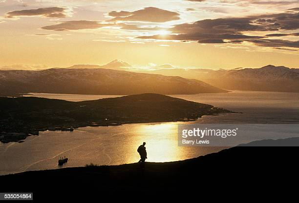 Silhouette of man on coastline during sunset in Tromso. For more than a century, the coastal steamer Hurtigruten has been the lifeline linking the...
