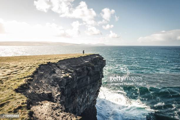 Silhouette Of Man On Rock By Sea Against Sky