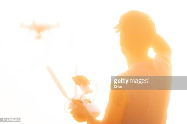 Silhouette of man operating drone