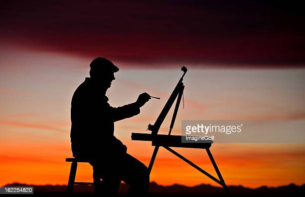 Silhouette of Man Painting with Easel at Sunset