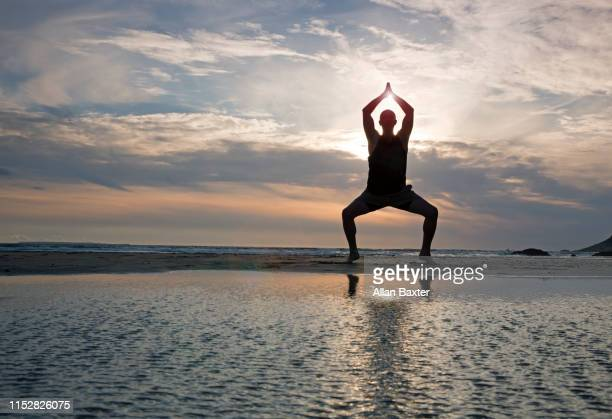 silhouette of man performing 'goddess pose' on beach - kung fu yoga stock pictures, royalty-free photos & images