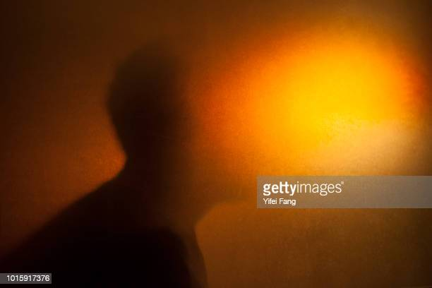 Silhouette of man profile behind translucent glass with orange hue