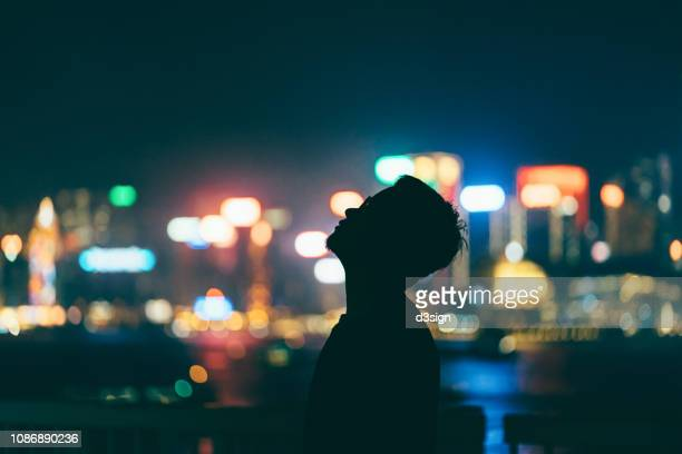 silhouette of man relaxing and looking up towards sky against illuminated and multi-coloured cityscape at night - prosperity stock pictures, royalty-free photos & images