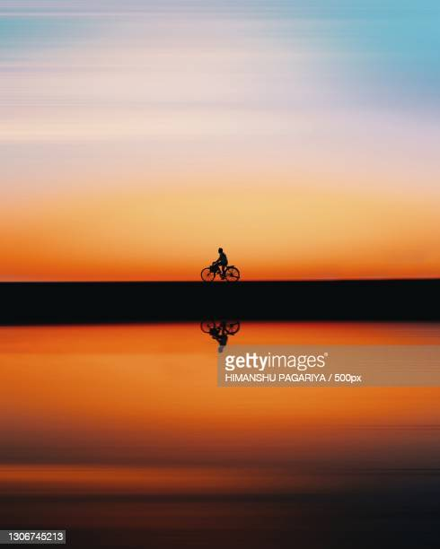 silhouette of man riding bicycle on road against sky during sunset - nature stock pictures, royalty-free photos & images