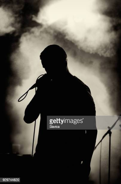 silhouette of man singing on the stage - pop musician stock photos and pictures
