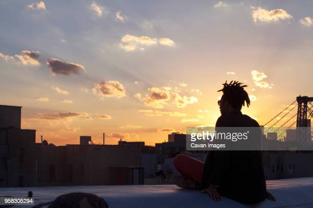 silhouette of man sitting on retaining wall against city - ドレッドロック ストックフォトと画像