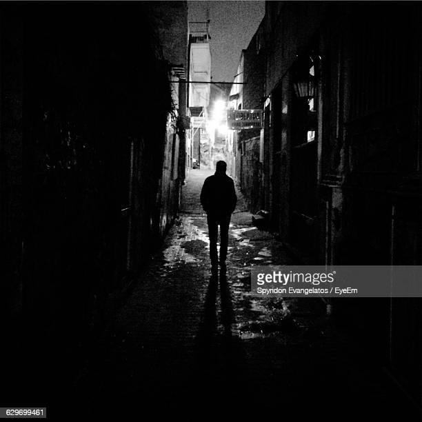 Silhouette Of Man Standing In Alley