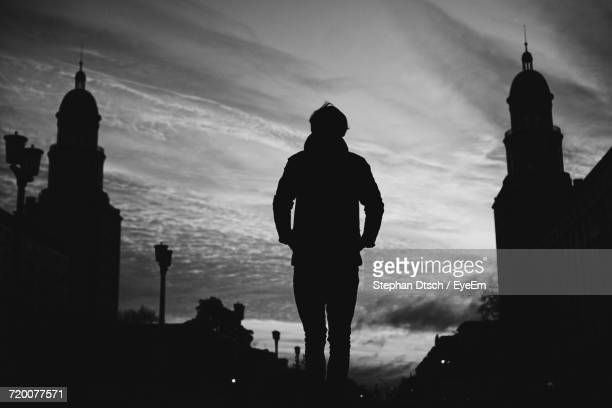 Silhouette Of Man Standing In City Against Sky