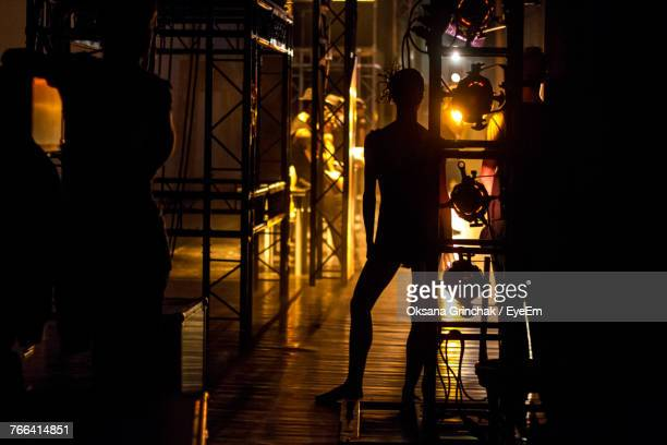 silhouette of man standing in illuminated room - kulisse bühne stock-fotos und bilder