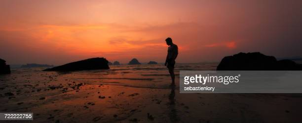 Silhouette of man standing on beach at sunset, Khao Lak, Thailand