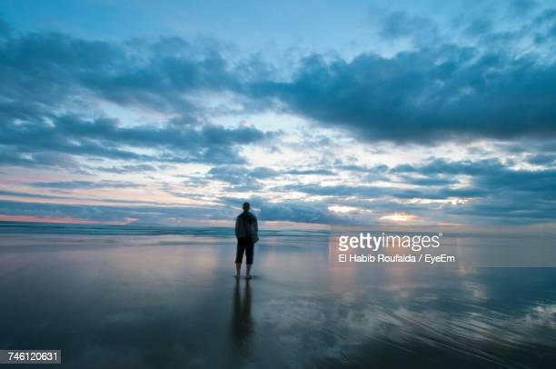silhouette of man standing on beach - tide stock pictures, royalty-free photos & images